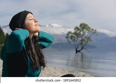 Young woman stretching her arms in front of Wanaka tree and enjoying morning sun. New Zealand.