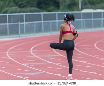 A young woman is stretching her legs after running