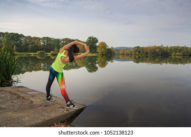 a young woman stretching for jogging at a lake