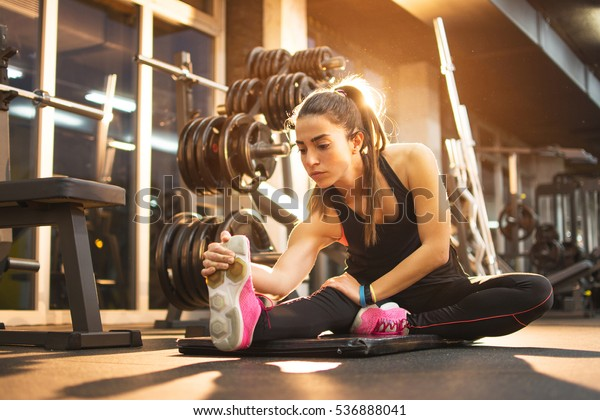 Young woman stretching legs in gym.