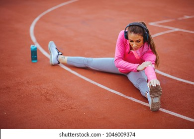 Young woman stretching legs on sports court outdoors
