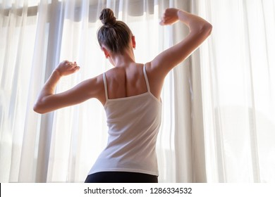 Young woman stretching near a window in apartment after wake up early in the morning. Start and the beginning a new day