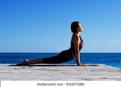 Young woman stretching on mat. Outdoors yoga. Cobra asana, bhujangasana on the beach. Sporty young woman leaning on hands, stretching legs. Healthy living.