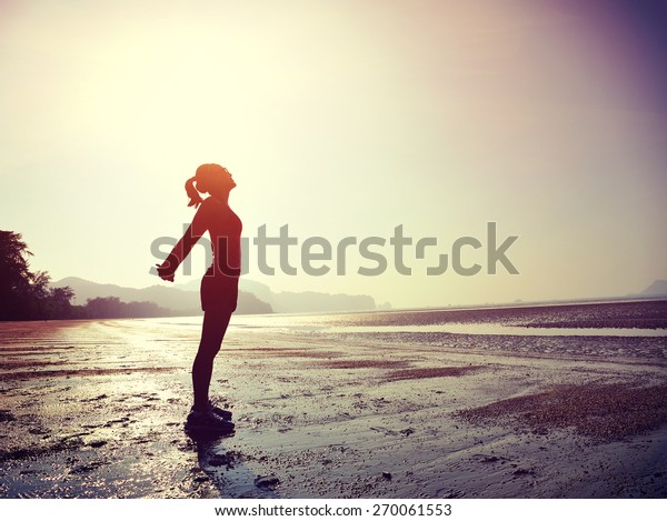 young woman stretching on  sunrise beach