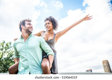 Young woman stretching out arms while sitting on the back of her boyfriend - Couple on a romantic date having fun outdoors