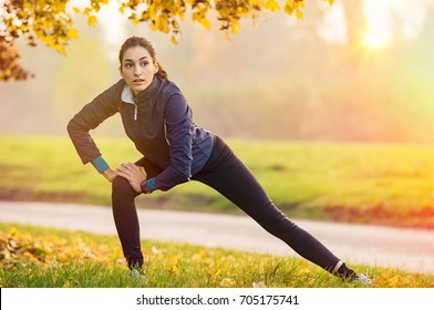 Young woman stretching and warming up at park during sunset. Attractive girl stretching before fitness in the autumn park. Beautiful sporty girl doing fitness outdoor during winter.