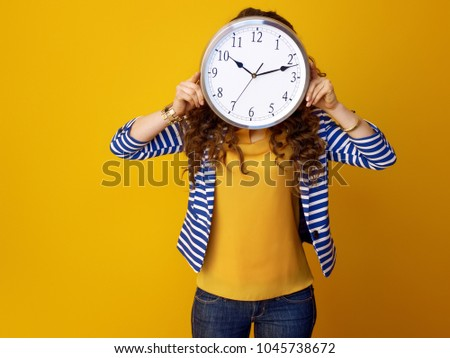 young woman in striped jacket isolated on yellow background holding clock in the front of face