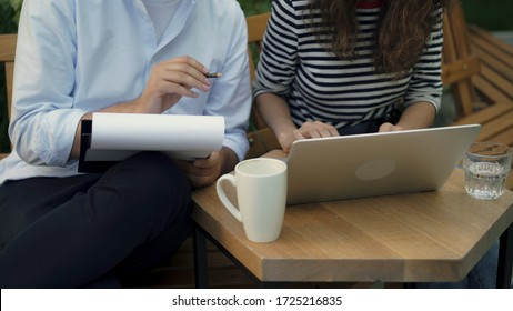 Young woman in striped shirt and her handsome colleague in white shirt working together in summer park using laptop and clipboard. The man is drinking coffee