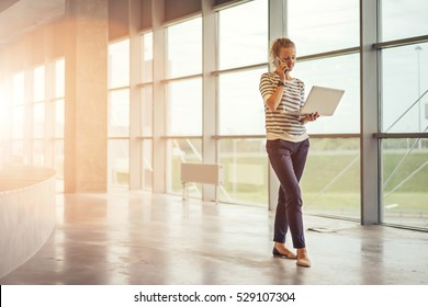 Young woman in striped shirt standing in room with modern interior near window and talking on cell phone while holding laptop.Girl uses gadget.Girl on phone discussing business issues.Film effect.
