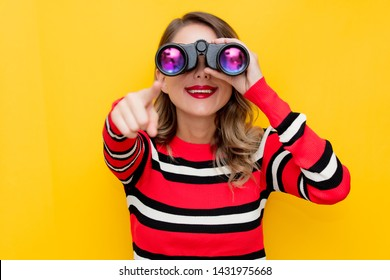 young woman in striped sweater with binocular on yellow background
