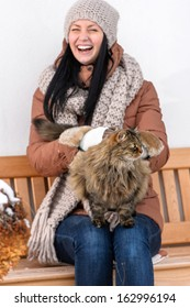 Young woman stroking cat sitting outside winter bench