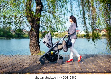 young woman with stroller on lake deck on city park. Happy mother walking child with pram