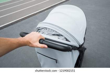 Young woman strolling a carriage outdoor. Closeup shot of male hands with grey stroller handle. Mother pushing the baby stroller around the city. Concept of active and fit parenting.