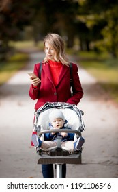 Young woman strolling in a park with stroller and a child in autumn season
