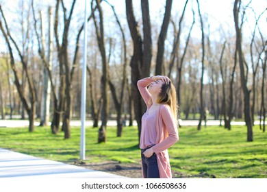Young woman strolling in park, wearing long light pink sweater and breathing fresh air. Concept of spring fashion look.