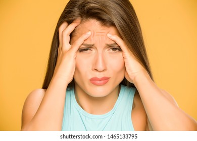 Young woman with strong headache on yellow background