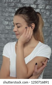 young woman struggles with earache, hand in the place of pain, side view