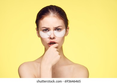 Young woman stuck patches under the eyes, skin care on a yellow background