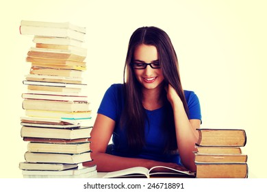 Young woman student with book by a desk.