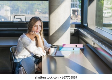 Young woman student with books and binders studying in a study area of university or college campus looking thoughtful to the side