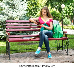 Young woman student sits in a park on a wooden bench and using tablet PC
