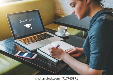 Young woman student sitting at table in cafe in front of laptop with inscription on screen e-learning and image of square academic cap and making notes in notebook,diary. Online education,e-learning.