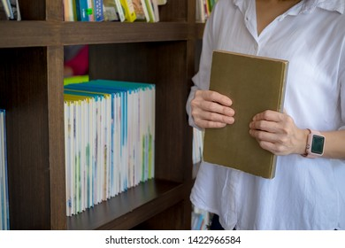young woman student standing in library holding books on her arms. education concept.