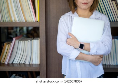 young woman student standing in library holding laptop on her arms. education concept.