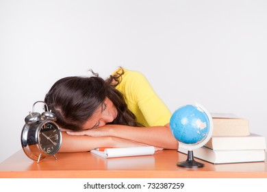 Young woman student, tired, falls asleep at desk