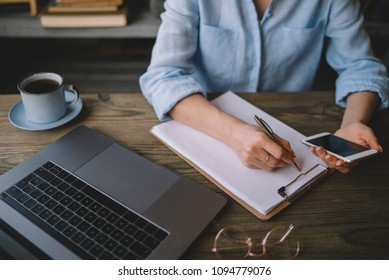 Young woman or student working on smart phone and writing on paper notebook, young woman using smart phone at home, online working from home concept. Close up of woman's hands making notes.