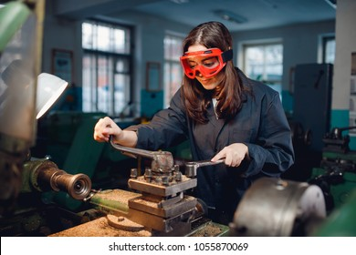 Young woman student works on an automatic lathe CNC, industrial workshop. Concept vocational education turner.