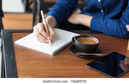 Young woman student writes information from portable net-book while prepare for lectures in University campus,hipster man working on laptop computer
