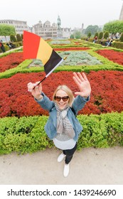 A young woman with a stunning smile and with the flag of Belgium in her hands is having fun in the park of the Mountain of Arts in Brussels. View from above. Student raised her hands up to the camera