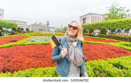 Young woman with a stunning smile and with the flag of Belgium in her hands having fun in the park of the Mountains of Arts in Brussels on the background of the old city.