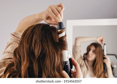 Young woman styling her shiny long brown hair with curling iron, looking at mirror at home. Selective focus, low depth of field