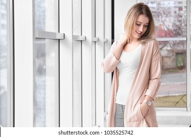 Young woman in stylish cardigan near window indoors