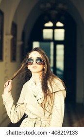 Young woman in stylish coat and glasses outdoor. Beauty and fashion, seasonal fashion