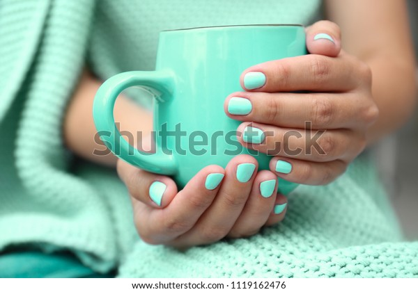 Young woman with stylish mint manicure holding cup, closeup