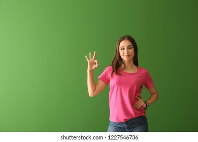 Young woman in stylish t-shirt showing OK gesture on color background