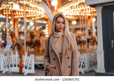 Young woman in a stylish warm autumn coat and a vintage knitted sweater stands in an amusement park in the city. Elegant fashion model girl.
