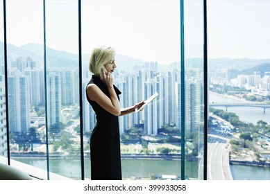 Young woman successful manager of big thriving company having cell telephone conversation,while is standing with touch pad in hand against cityscape view outside office window.Copy space for content