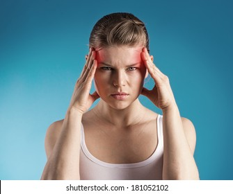 Young woman suffer from dizziness or vertigo holding her head. Portrait of exhausted female with migraine problem over blue background.