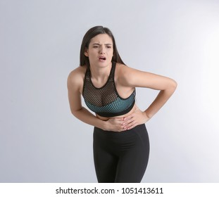 Young woman suffering from abdominal pain on light background
