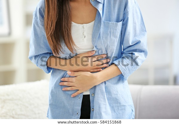 Young woman suffering from abdominal pain at home, closeup. Gynecology concept