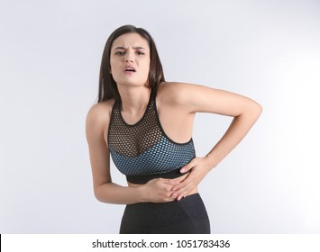 Young woman suffering from flank pain on light background
