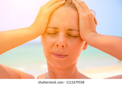 Young woman suffering with headache. Woman on hot beach with sunstroke. Health problem on holiday. Medicine on vacation. Dangerous sun. Beach life. Sunstroke on sunny beach. Healthcare in tropics