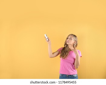 Young woman suffering from heat on color background. Air conditioner malfunction