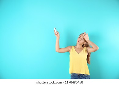 Young woman suffering from heat on color background with copy space text. Air conditioner malfunction