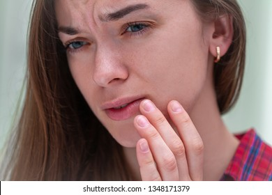 Young woman suffering from herpes on lips. Treatment of herpes infection and virus