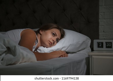 Young woman suffering from insomnia in bed at home
